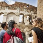 Guide explaining to tourists the Coliseum of Rome