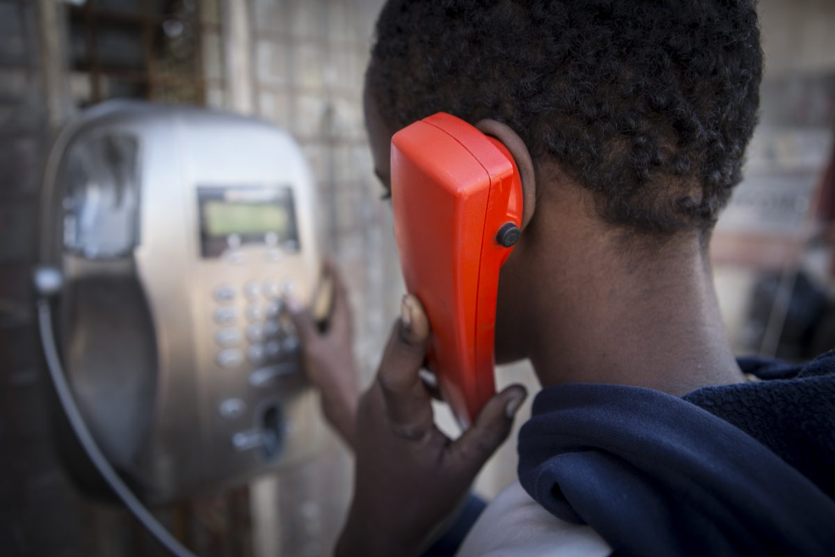 Young migrant boy making a phone call at the reception center in