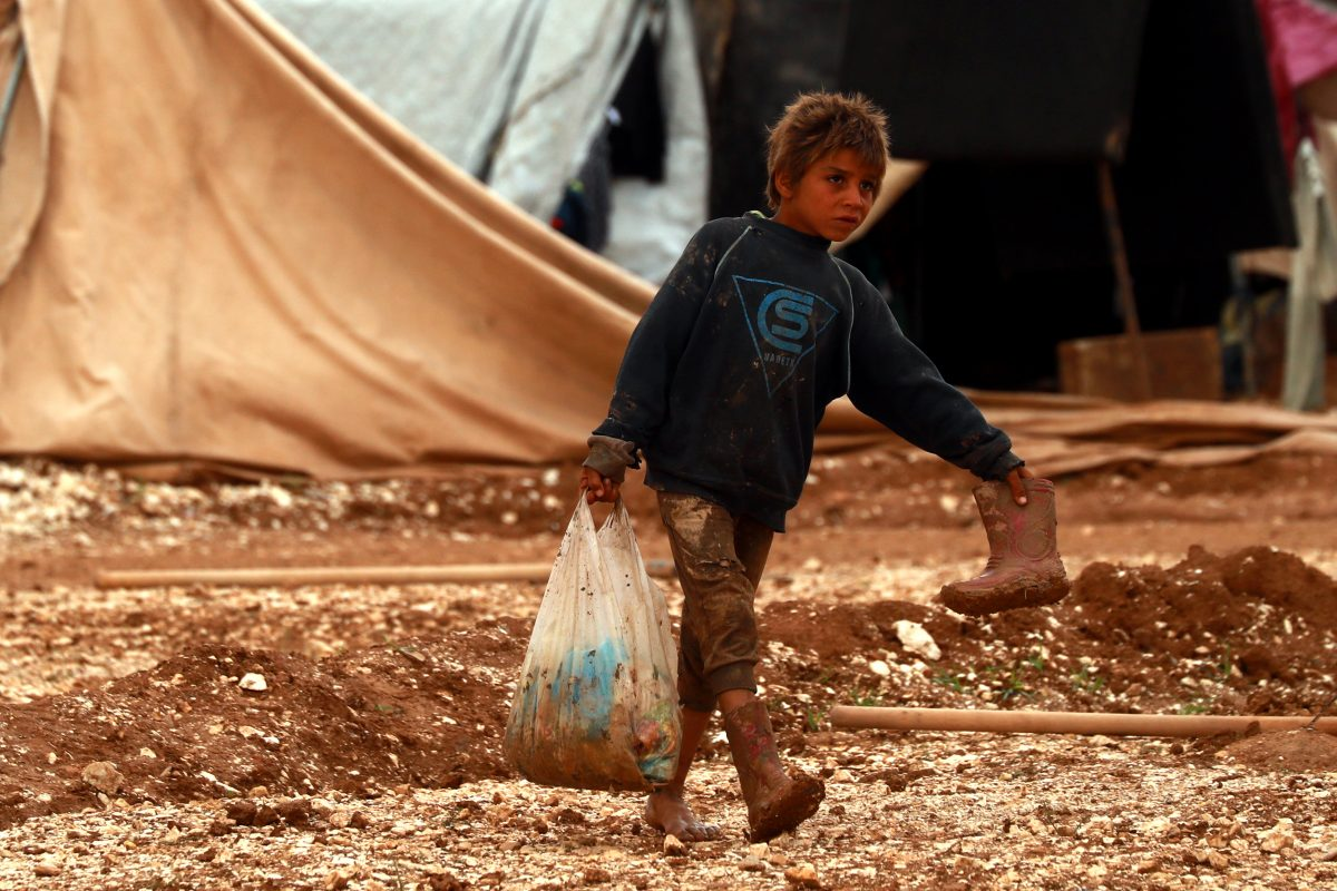 """Ahmad, 12, carries supplies through Areesheh, a northeastern tented camp for Internally Displaced Persons (IDPs), Al-Hasakah  Governorate, Syrian Arab Republic, 15 November 2018. Originally from Homs, Ahmad has been displaced several times over the past few years, finally reaching Areesheh camp last year. """"We need a new tent to protect us from the rain and fuel for heating,"""" he says of his family's situation. For the 13,000 people who currently live in Areesheh, in the middle of the desert, winter comes with added harshness. Having fled escalating violence over the past two years with few belongings, these children and their families are living in basic conditions, lacking warm clothes, blankets or heating."""