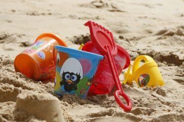 bambini giochi spiaggia secchiello