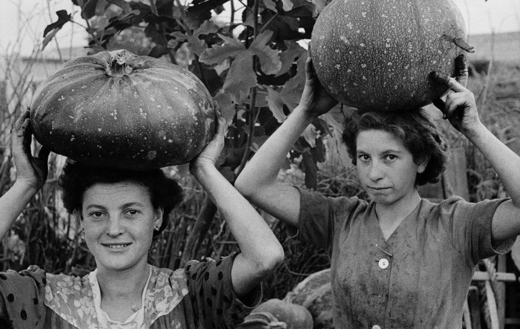 ANDO GILARDI Giovani donne portano zucche sulla testa