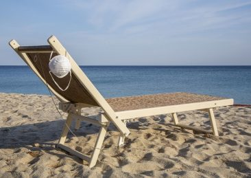 Protective mask on the beach chair. Desert beach due to Coronavirus (Covid19) quarantine. Campo nell'Elba, Italy